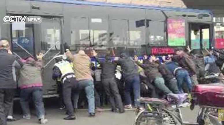 Watch a group of people lift a bus off a trapped man